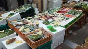 Un étal de légumes dans un marché couvert typique. Emballés dans du plastique, vendus en petite quantité.